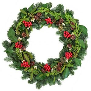 Christmas wreath with holly, ivy, mistletoe and winter greenery over oak background.